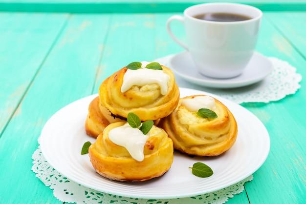 Vers gebakken, kwarkbroodjes, met room en muntblaadjes en kopje thee op een witte plaat