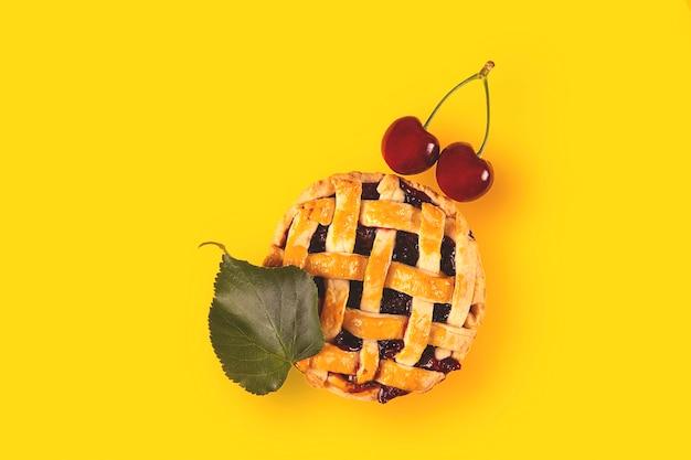 Vers gebakken mini-kersentaart is een zelfgemaakte herfstmaaltijd met rijpe kersen en herfstblad op geel