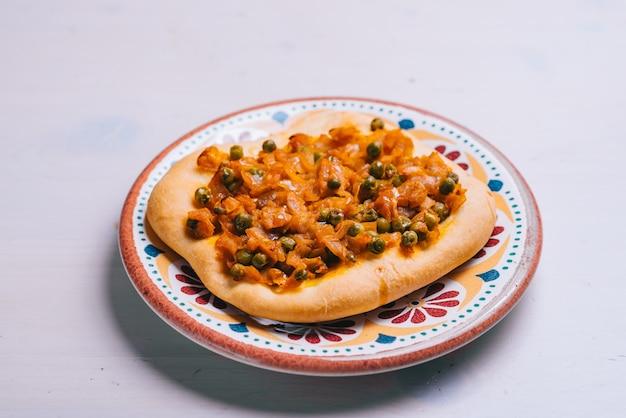 Vers gebakken minipizza met doperwtjes en worteltjes en uien. traditioneel spaans gebak met groenten.