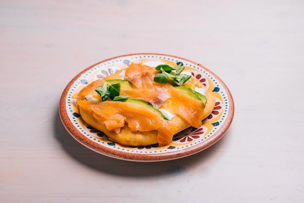 Vers gebakken minipizza met zalm en olie. traditioneel spaans gebak met groenten.