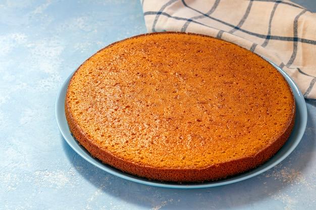 Vers gebakken ongesneden wortel taart, citroentaart of griesmeel cake op blauw bord.