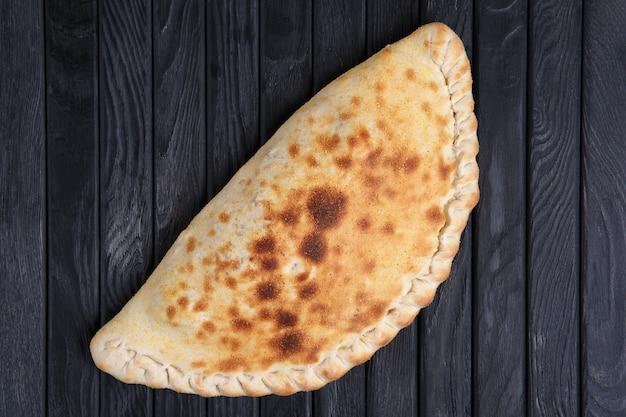 Vers gebakken pizzacalzone op donkere houten lijst, hoogste mening.