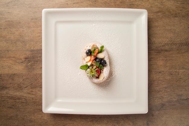 Vers gebakken pompoenchurros met rood fruit op plaat.