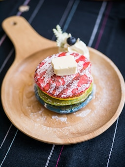 Vers gebakken rainbow pancake met poedersuiker en boter