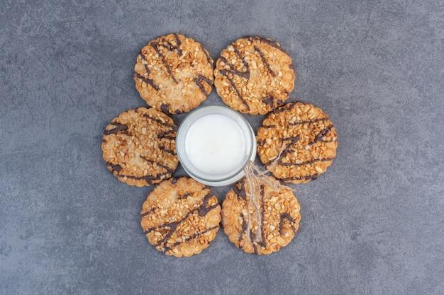 Vers gebakken sesamzaadjes koekjes en melk op marmeren tafel.