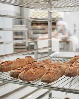 Vers gebakken stokbrood op een koelrek in het interieur van een bakhuis
