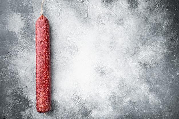 Vers gebakken worst salami set, op grijze stenen tafel, bovenaanzicht plat gelegd