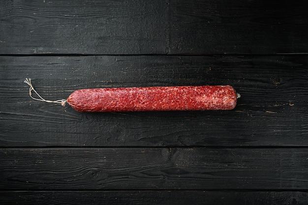 Vers gebakken worst salami set, op zwarte houten tafel, bovenaanzicht plat lag