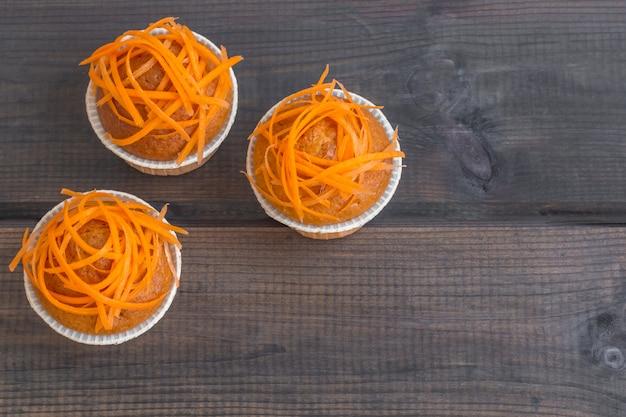 Vers gebakken wortelmuffins die met verse wortelspaanders worden verfraaid op houten achtergrond. nationale carrot cake day.