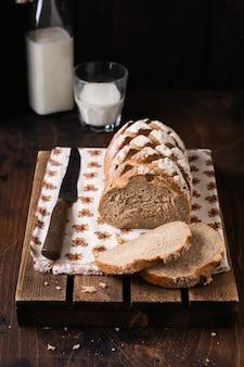 Vers gebakken zelfgebakken brood met melk op een oude houten tafel. rustieke stijl.