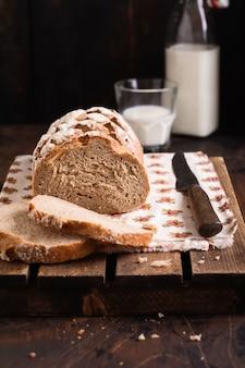 Vers gebakken zelfgebakken brood met melk op een oude houten tafel