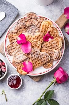 Vers gebakken zelfgemaakte hartvormige belgische wafels op een grijze achtergrond. europese gebakken gebakjessnoepjes