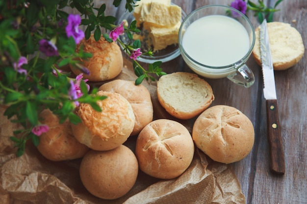 Vers gebakken zelfgemaakte roggebroodjes en glas melk op houten tafel in rustieke stijl