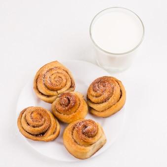 Vers gebakken zelfgemaakte slakkenbroodjes met suiker en kaneel met melk in glas