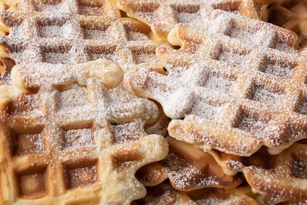 Vers gebakken zelfgemaakte wafels bestrooid met poedersuiker geruit gestructureerd oppervlak. ongezond eten, streetfood