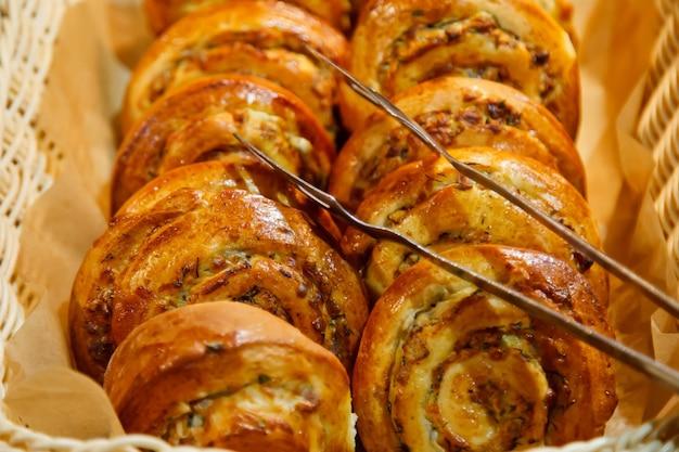 Vers gebakken zoete bladerdeegbroodjes met chocolade en kokoskruimels in houten rieten mand zijn klaar om te eten. concept van ontbijt of brunch. achtergrond voor website of banner. ruimte kopiëren