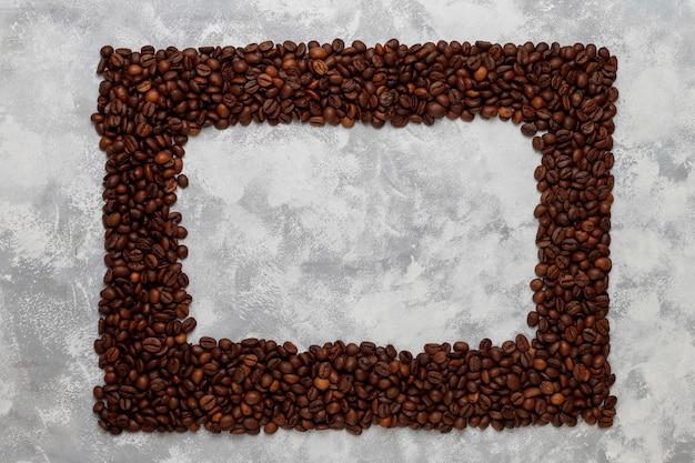 Vers gebrande koffiebonen op beton, bovenaanzicht, plat lag