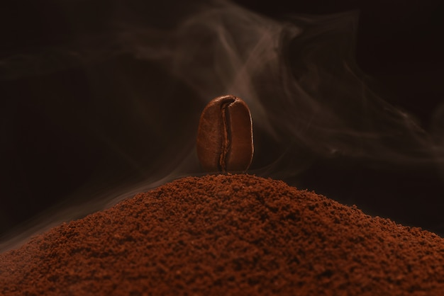 Vers gebrande koffieboon staat op een verstrooiing van handvol koffie in de rook