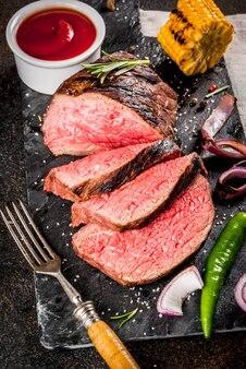 Vers gegrild rundvlees, zelfgemaakt bbq-vlees medium zeldzaam, op zwarte stenen snijplank, met kruiden