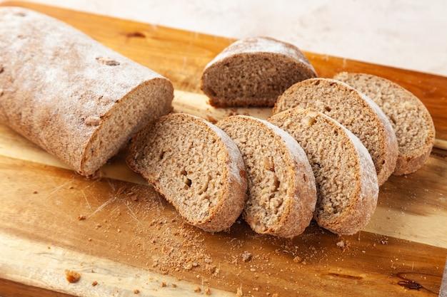 Vers gehakt bruin roggebrood, plakjes op houten snijplank, ontbijtconcept, horizontaal, kopie ruimte, plaats voor tekst