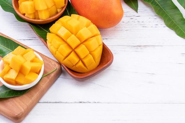 Vers gehakte mango op een dienblad en lichte rustieke houten tafel.