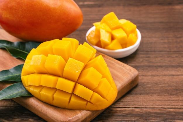 Vers gehakte mangoblokjes op houten snijplank