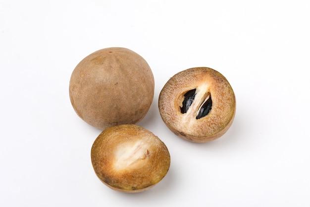 Vers geheel en de helft van geïsoleerd sapodillafruit