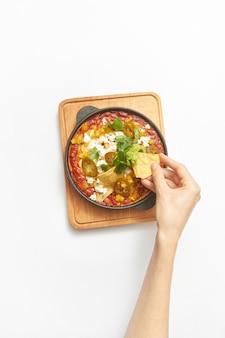 Vers gekookt traditioneel gerecht shakshuka van gebakken eieren met tomaten, paprika, groenten en kruiden in een pan met vrouw hand boven houten bord op een lichtgrijze achtergrond, kopieer ruimte. bovenaanzicht.