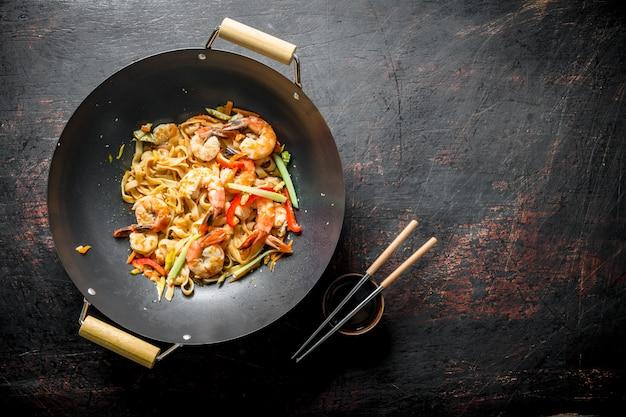 Vers gekookte aziatische udon-noedels met groenten en garnalen op zwarte rustieke lijst