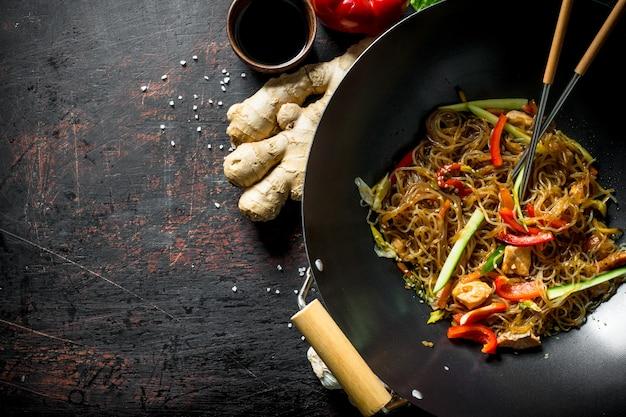 Vers gekookte chinese noedels wok funchoza met zalm, groenten en saus op donkere houten tafel