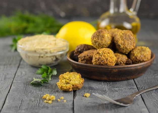 Vers gekookte falafel op klei kom op een houten tafel met tahin saus en olie