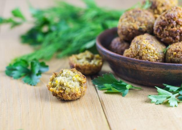 Vers gekookte falafel op slabladeren op een houten tafel met tahin saus