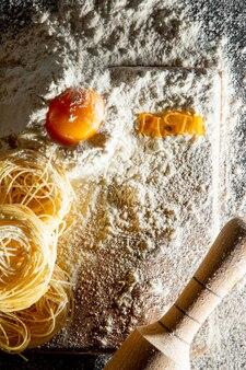 Vers gekookte pasta ligt op een donker met bloem bestrooid oppervlak. italiaanse pasta. tagliatelle. rauwe pasta. italiaans pastarecept. bovenaanzicht, kopieer ruimte.