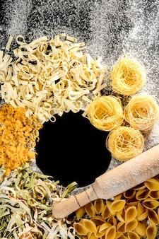 Vers gekookte pasta ligt op een donker oppervlak bestrooid met bloem. italiaanse pasta. tagliatelle. rauwe pasta. italiaans pastarecept. bovenaanzicht, kopieer ruimte.