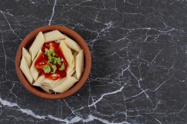 Vers gekookte pennedeegwaren met worstplakken en ketchup in houten kom.
