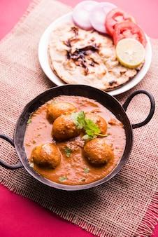 Vers gekookte pittige aardappelcurry in koekenpan of hete en pittige dum aloo geserveerd met tandoori roti of naan of indiaas brood of chapati en groene salade, selectieve focus