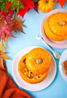 Vers gekookte pompoensoep geserveerd in een pompoen. gevulde pompoen. herfst warm en gezellig eten. bovenaanzicht.