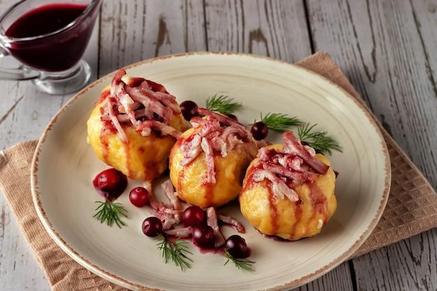 Vers gekookte zweedse aardappelbollen met cranberrysaus op een lichte achtergrond.