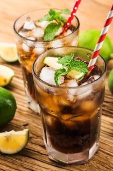 Vers gemaakt cuba libre met bruine rum, cola, munt en citroen op houten oppervlak