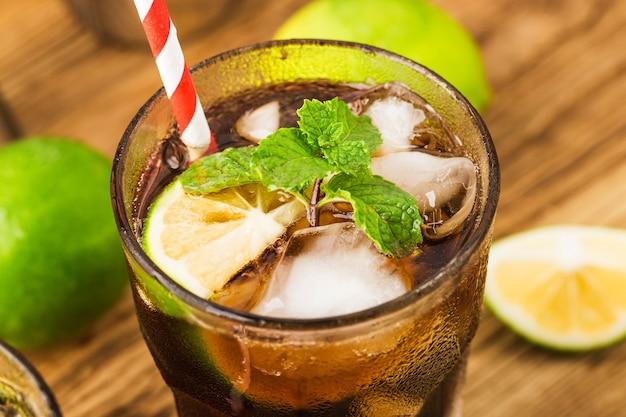 Vers gemaakt cuba libre met bruine rum, cola, munt en citroen op houten tafel