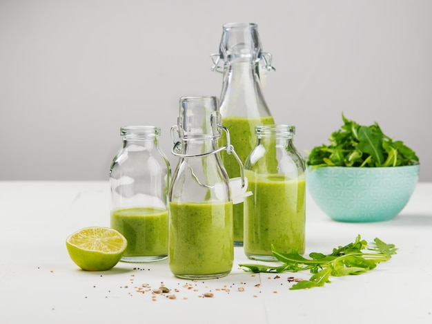 Vers gemaakt gezond groen smoothie geserveerd in flessen op witte achtergrond.