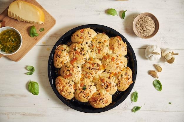 Vers gemaakt heerlijk kaasbel pizzabrood met ingrediënten en kaas op een witte tafel
