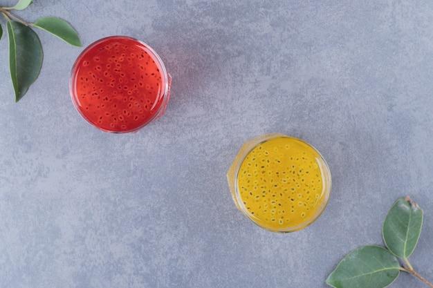 Vers gemaakt sinaasappel- en granaatappelsap op een grijze achtergrond.