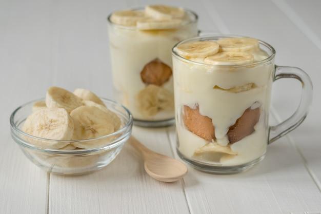 Vers gemaakte bananenpudding in de cirkels en de plakjes banaan op een witte tafel.