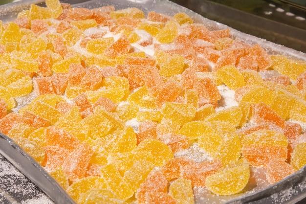 Vers gemaakte fruitgumdrops in suiker liggen op een dienblad in een banketbakkerij