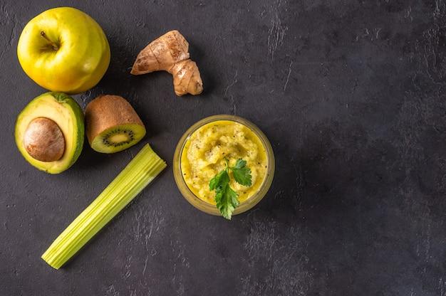 Vers gemaakte groene smoothie gemaakt van gember avocado appel kiwi selderij appels kruiden en groenten