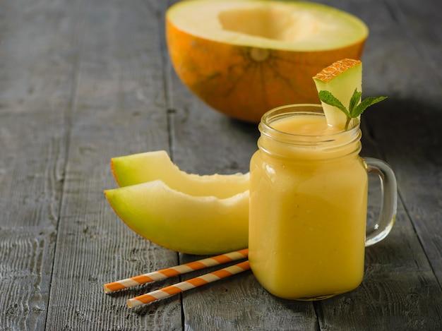 Vers gemaakte meloen, sinaasappel en bananenmoothies en twee cocktailbuizen op donkere houten tafel.