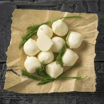 Vers gemaakte mozzarellakaas met dille op een houten lijst