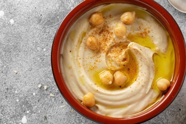 Vers gemaakte oosterse klassieke hummus geserveerd in een kom op tafel.