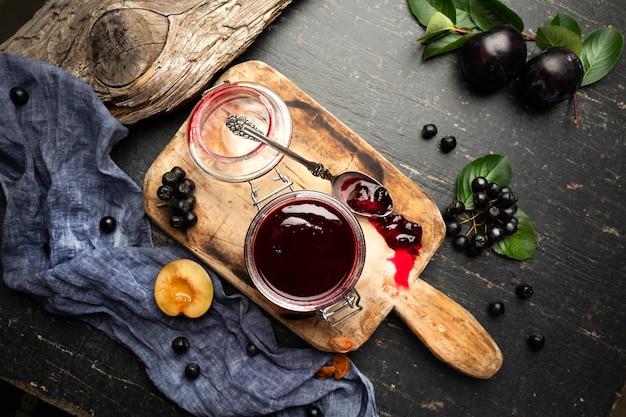 Vers gemaakte pruimenjam in een pot en fruit op een tafel met gordijnen.